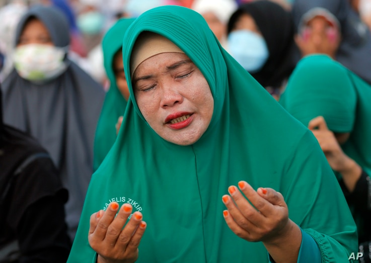 A Muslim woman prays during a special prayer for the victims of earthquake and tsunami at Talise beach in Palu, Central Sulawesi, Indonesia, Oct. 5, 2018.