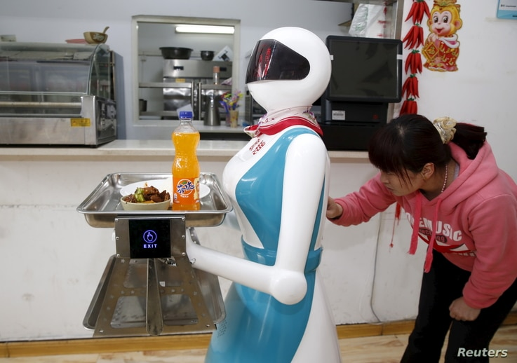 A woman input orders for a robot which works as a waitress in a restaurant in Xi'an, Shaanxi Province, China, April 20, 2016.