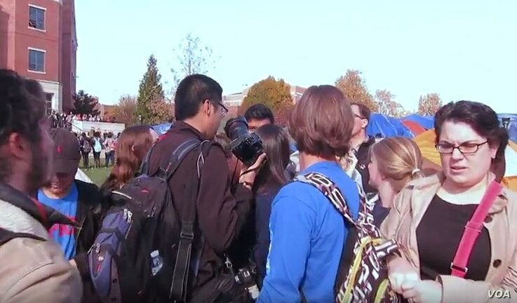 University of Missouri student photographer Tim Tai is blocked from taking photographs by student protesters in Columbia, Missouri, Nov. 9, 2015.