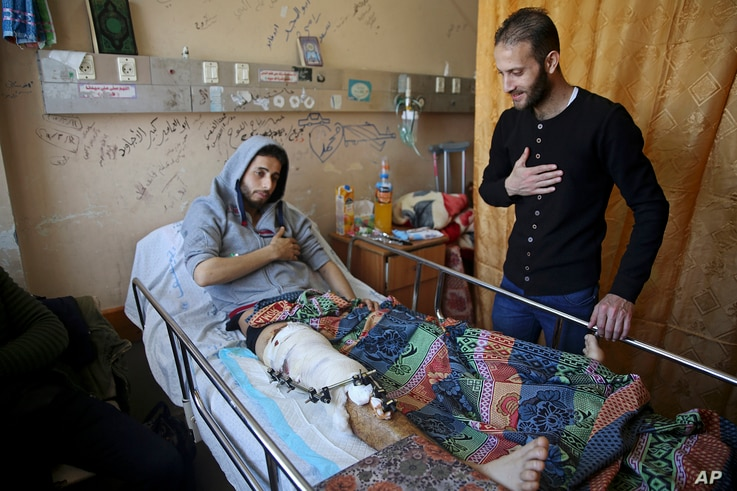 Mahmoud Barakat, lies in bed as a friend visits him at the Shifa hospital in Gaza, April 9, 2018. Barakat is among the nearly 1,300 people that Palestinian health officials said have been shot and wounded by Israeli soldiers during mass border protes...