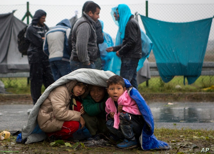 Children take shelter from the rain in Sredisce ob Dravi, a border crossing between Croatia and Slovenia, Oct. 19, 2015.