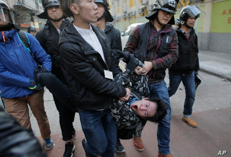 A rioter is taken away by police on a street at Mong Kok district of Hong Kong, Feb. 9, 2016.