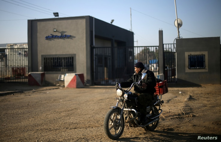A Palestinian rides a motorcycle outside Kerem Shalom, the main passage point for goods entering Gaza, after it was shut down by Israel, in the southern Gaza Strip, Jan. 14, 2018.