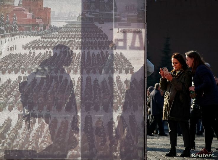 FILE - People are seen near a poster after a military parade in Red Square, Moscow, Russia Nov. 7, 2018.