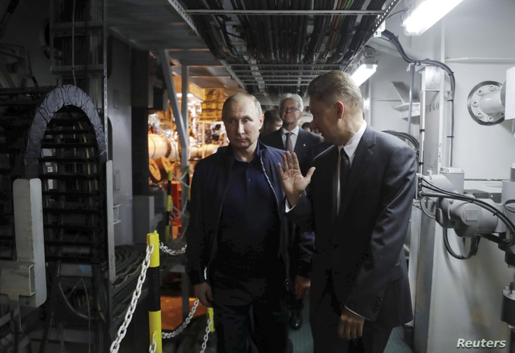FILE - Russian President Vladimir Putin and Gazprom Chief Executive Alexei Miller inspect the work on the Turkish Stream gas pipeline project aboard the Pioneering Spirit pipeline-laying ship in the Black Sea near Anapa, Russia, June 23, 2017.