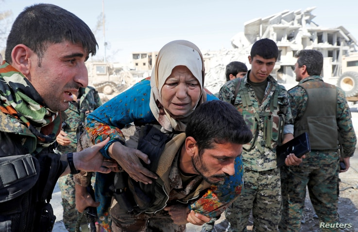 Fighters of Syrian Democratic Forces (SDF) evacuate a civilian in Raqqa, Syria, Oct. 17, 2017.