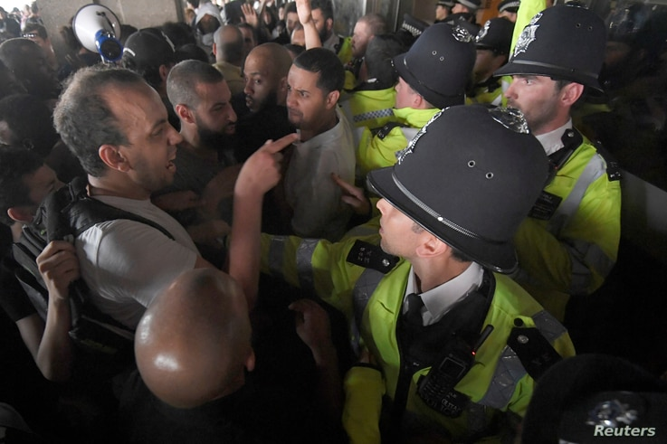 Police officers confront demonstrators inside Kensington Town Hall, during a protest following the fire that destroyed The Grenfell Tower block, in north Kensington, West London, Britain, June 16, 2017.