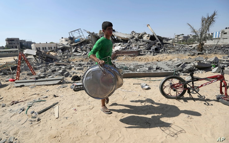 A Palestinian salvages what he can from a house after it was hit by an Israeli missile strike in Rafah, southern Gaza Strip, July 9, 2014.
