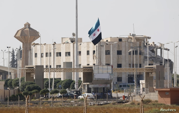 A Syrian independence flag and the damaged customs office at Syria's Tel Abyad border gate are pictured from the Turkish town of Akcakale, October 5, 2012.