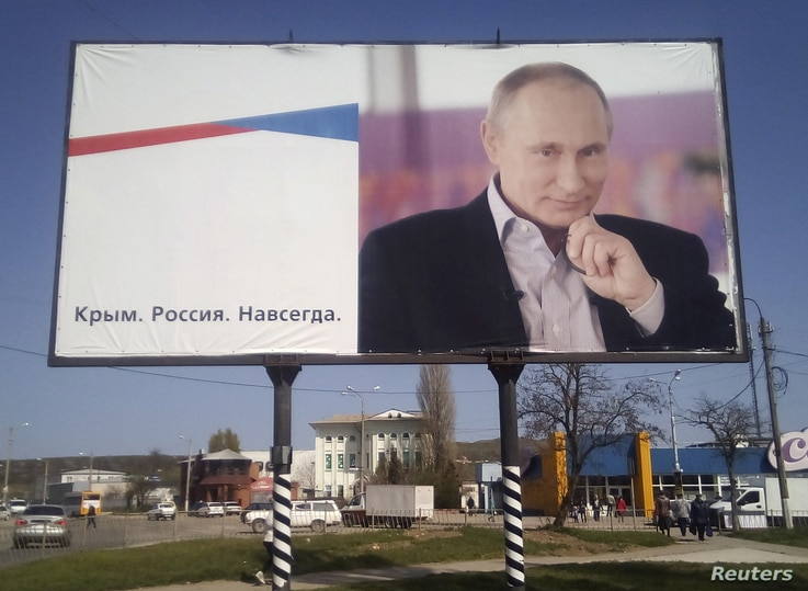 """FILE - A billboard with a portrait of Russian President Vladimir Putin is displayed on a street in Kerch, Crimea, April 7, 2016.  The board reads: """"Crimea. Russia. Forever."""""""