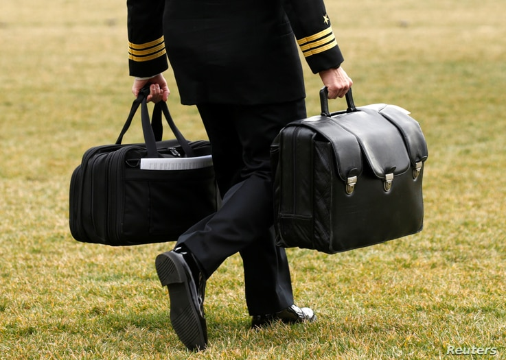 """A military aide, carrying the """"football"""" containing launch codes for nuclear weapons, accompanies U.S. President Donald Trump onto Marine One upon Trump's departure from the White House in Washington,  Feb. 3, 2017."""
