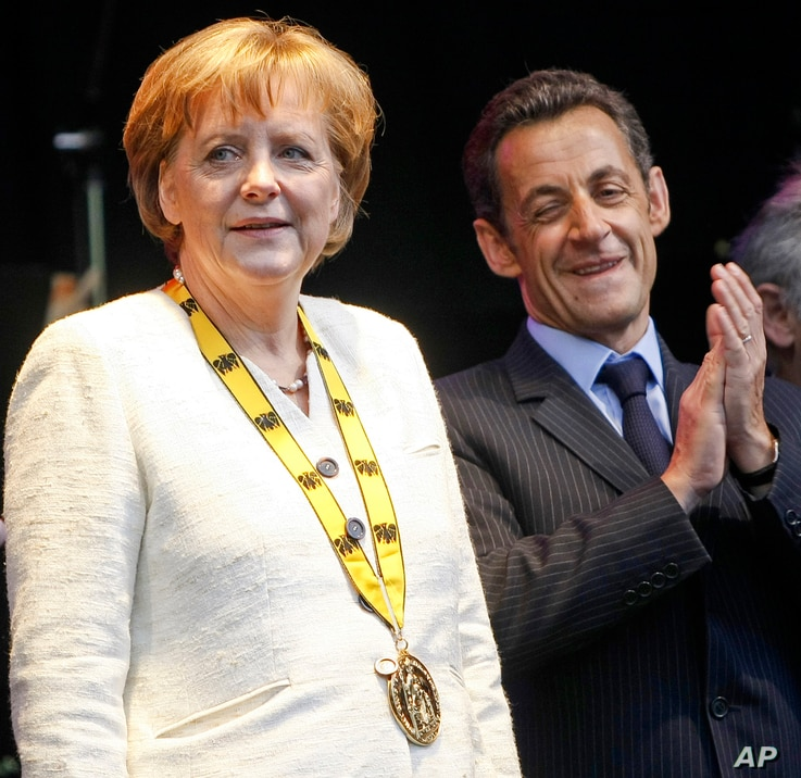 On May 1, 2008, German Chancellor Angela Merkel and then-French President Nicolas Sarkozy stand on a stage after the Charlemagne Prize was awarded to Merkel  in Aachen, Germany.