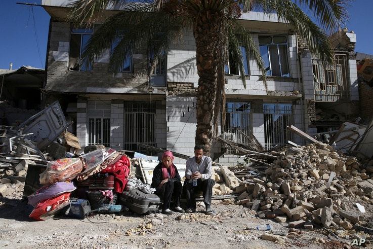 Survivors sit in front of a destroyed house on the earthquake site in Sarpol-e-Zahab in western Iran, Nov. 14, 2017.