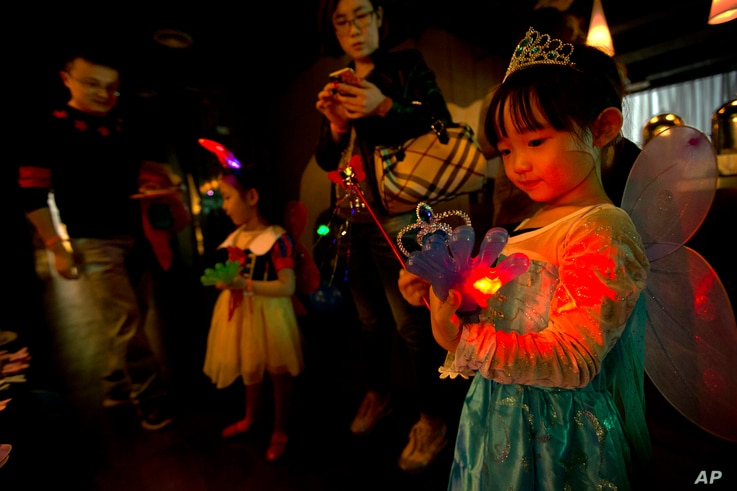 FILE - a girl plays with an electronic toy while standing with her family at a Mother's Day-themed disco dance party for children in Beijing.