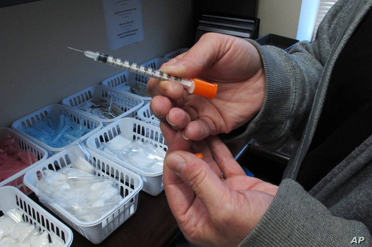 FILE - Paula Maupin, the public health nurse for eastern Indiana's Fayette County, holds one of the syringes provided to intravenous drug users taking part in the county's state-approved needle exchange program, which is housed in the county courthou