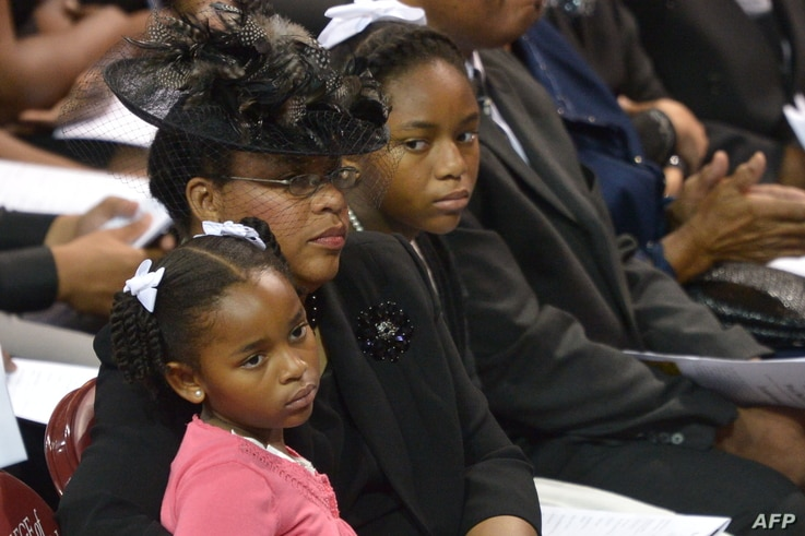 The wife of South Carolina State Sen. and Rev. Clementa Pinckney, Jennifer, sits with daughters Malana and Eliana (R) during his funeral, at the College of Charleston TD Arena, in Charleston, South Carolina, June 26, 2015.