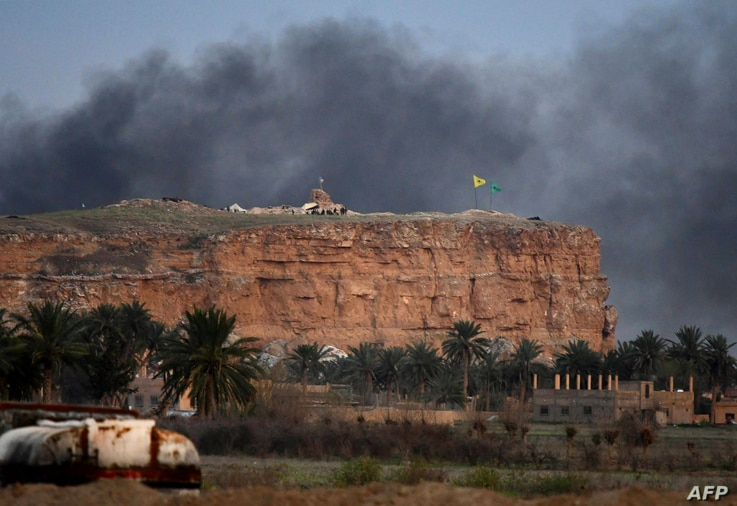 This picture taken on March 22, 2019 shows smoke rising over the village of Baghuz in the eastern Syrian province of Deir Ezzor, with the flags of the Kurdish People's Protection Units (Yellow) and Women's Protection Units (Green) seen flying at one ...
