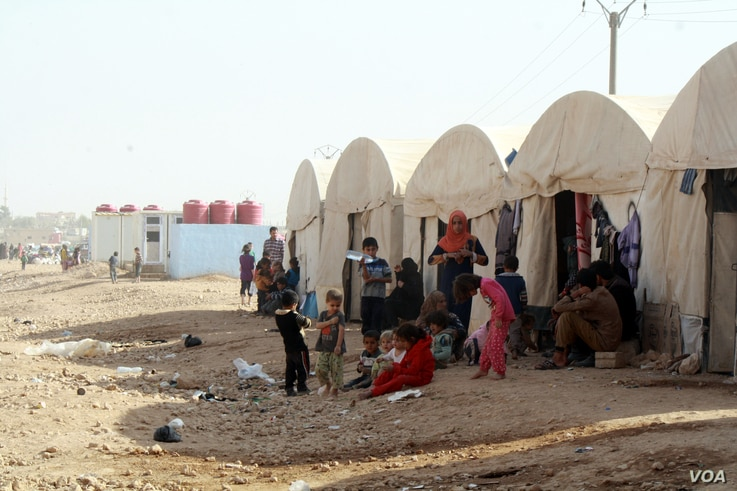 After he was released and cleared, Yazan moved into these large tents with neighbors from Raqqa who also escaped recently on Oct. 25, 2017 in Ain Issa, Syria (H.Murdock/VOA)