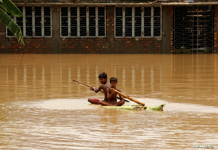 Boys row a makeshift raft at a flooded village in Howrah district, West Bengal, India Aug. 2, 2017.