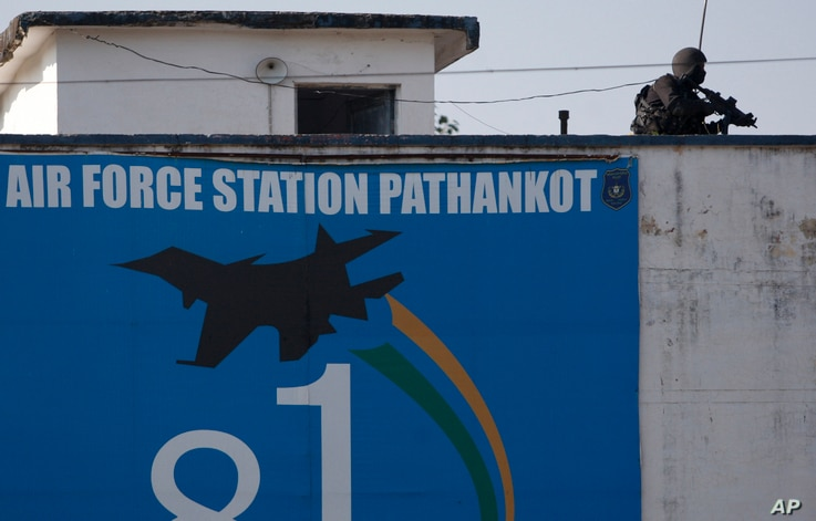An Indian military commando is seen on the top of a building at the Indian air force base in Pathankot, India, Jan. 5, 2016, following a militant attack on the base.