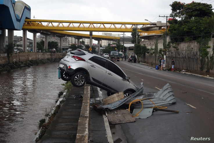 A car is nearly pushed into a channel after heavy rains in Vila Prudente neighborhood in Sao Paulo, Brazil, March 11, 2019.
