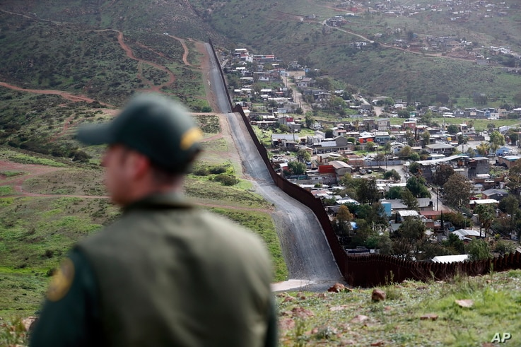 Border Patrol agent Vincent Pirro looks on near a border wall that separates the cities of Tijuana, Mexico, and San Diego, Feb. 5, 2019, in San Diego.