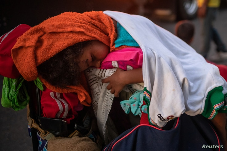 A young migrant, traveling with a caravan of thousands from Central America en route to the United States, sleeps atop baggage resting on a stroller while looking to go to Arriaga from Pijijiapan, Mexico, Oct. 26, 2018.