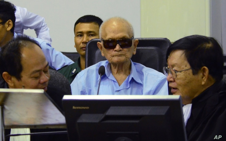 In this photo released by the Extraordinary Chambers in the Courts of Cambodia, Nuon Chea, center, who was the Khmer Rouge's chief ideologist and No. 2 leader, sits in the court room during a hearing at the U.N.-backed war crimes tribunal, in Phnom P...