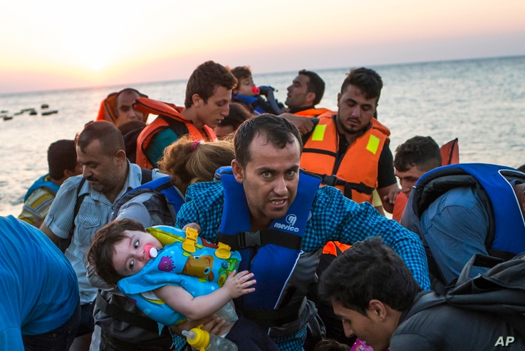 A man carries a girl in his arm as migrants arrive at a coast on a dinghy after crossing from Turkey in the southeastern island of Kos, Greece, during the sunrise early on Aug. 13, 2015.