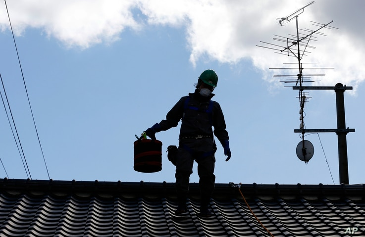 FILE - A worker wearing cleans radiation-exposed roof tiles at a private house in Minamisoma, Fukushima prefecture, northeastern Japan, Feb. 24, 2016. About 7,000 day laborers are cleaning up this irradiated town north of the Fukushima nuclear plant....