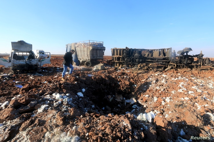 FILE - A man inspects a hole in the ground near damaged trucks at a site hit by what activists said were airstrikes carried out by the Russian air force in Karf Naseh town, Aleppo countryside, Syria, Dec. 26, 2015.