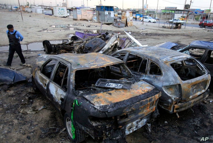 A police officer inspects the aftermath of a car bomb attack at a used car dealer's parking lot in Habibiya, Baghdad, Iraq, April 16, 2013.