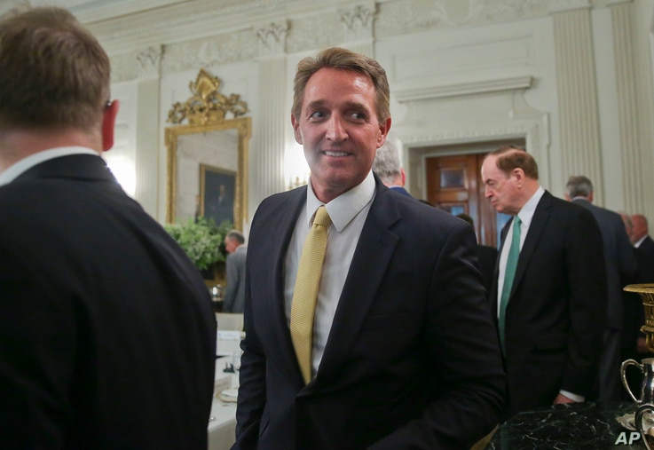 FILE - Sen. Jeff Flake, R-Ariz., center, walks to his seat as he attends a luncheon with other GOP senators and President Donald Trump, July 19, 2017, in the State Dinning Room of the White House in Washington.