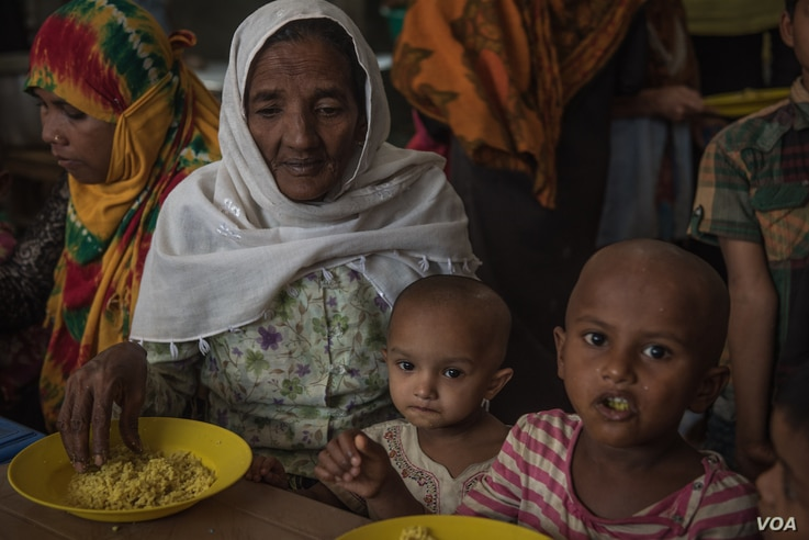 A Rohingya refugee family eats a free lunch given out by Action Against Hunger in Ukhiya, Bangladesh, April 19, 2018. Many families depend on the hot meals handed out by the aid group.