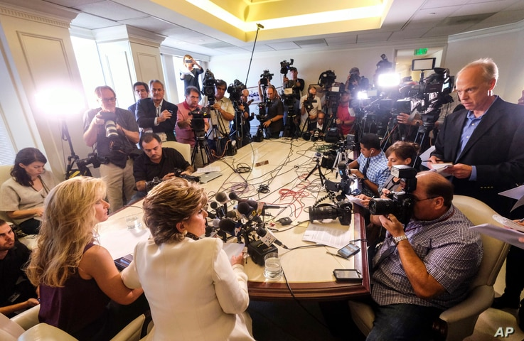 """Summer Zervos, foreground left, alongside her attorney Gloria Allred, foreground center, addresses the media during a news conference in Los Angeles, Oct. 14, 2016. Zervos, a former contestant on """"The Apprentice"""" says Republican presidential candidat..."""
