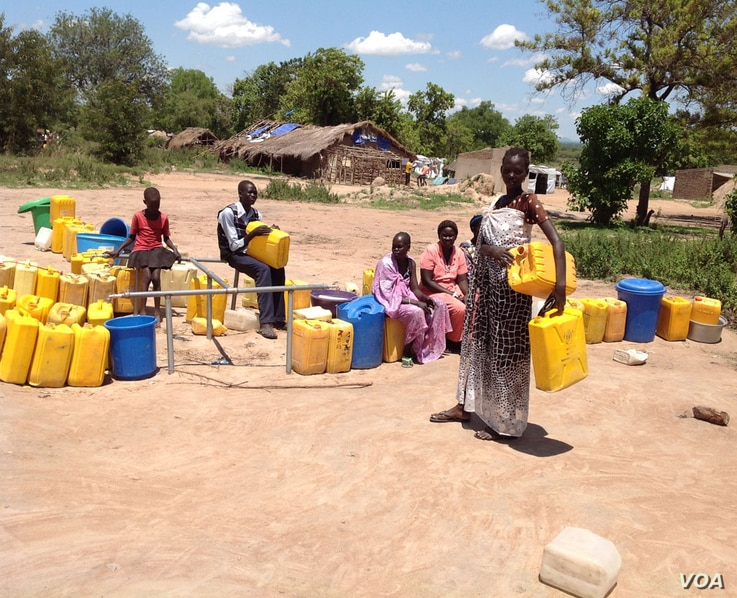 A woman refugee waits to add her jerry cans to the long line at a watering hole in a Uganda refugee settlement housing thousands of South Sudanese.