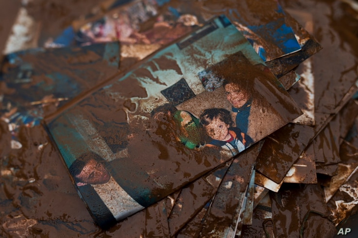 Family pictures are covered with mud after flood water has receded outside a house in the town of Mandra, Greece, Nov. 16, 2017.