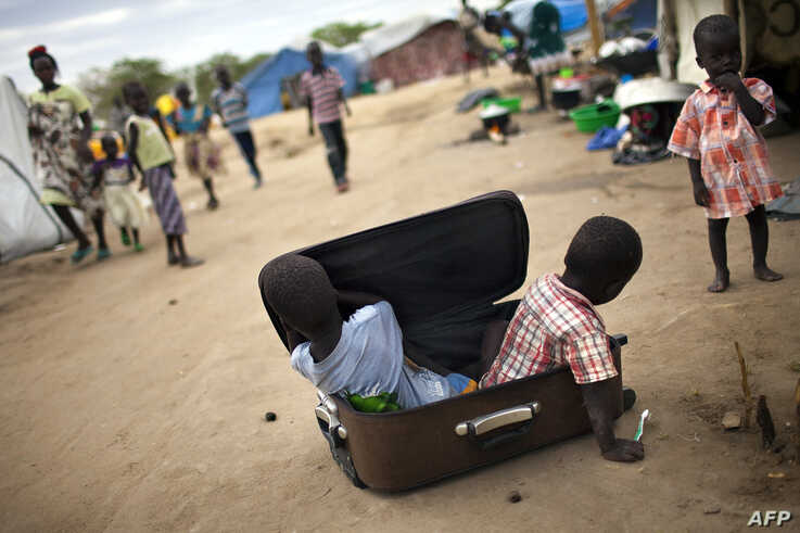 Children play with a suitcase in a IDP camp for the Nuer ethnic group inside the UNMISS compound in Bor, South Sudan, on February 27, 2014.