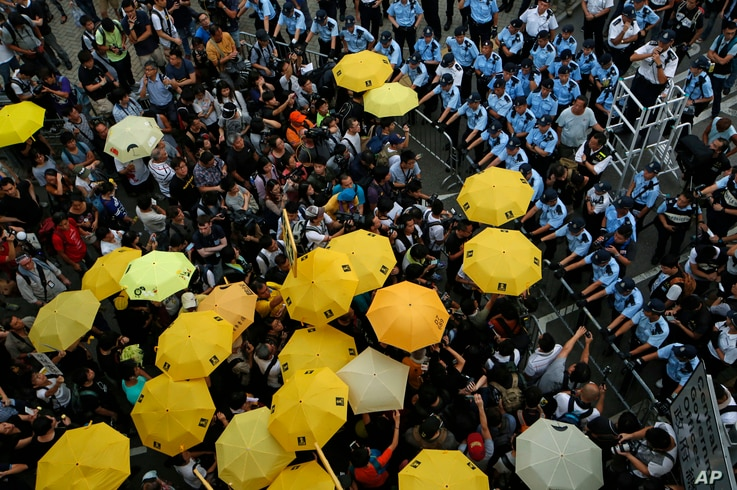 """Protesters holding yellow umbrellas gather to observe a moment of silence to mark the first anniversary of """"Umbrella Movement"""" outside the government headquarters in Hong Kong, Sept. 28, 2015."""