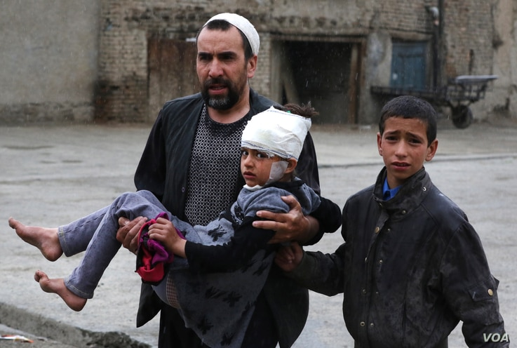 An Afghan man carries a girl who was injured in a suicide bomb blast that targeted the premises of the Ministry of Defense, in Kabul, Afghanistan, 19 April 2016.