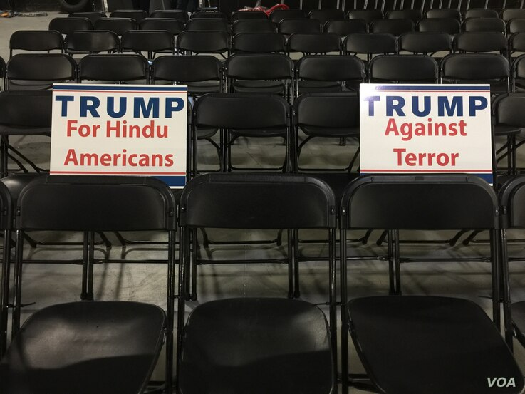 Signs provided by organizers rest on chairs in the hall ahead of Donald Trump's speech to Hindu Americans. (E. Sarai/VOA)