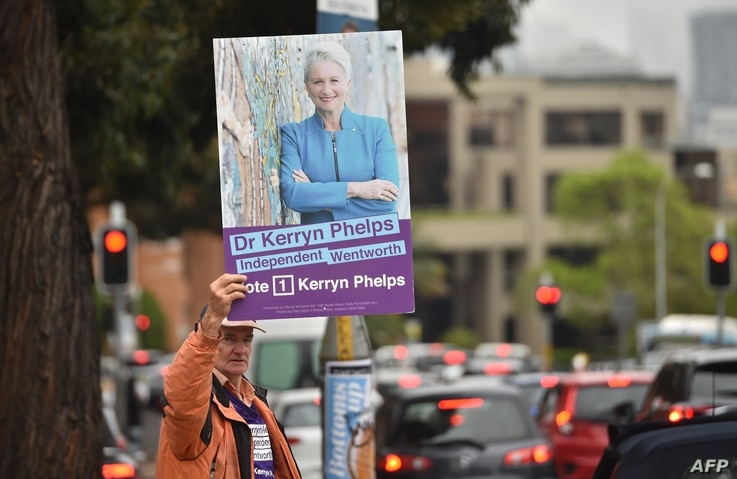 A supporter of high-profile independent candidate for Sydney's Wentworth electoral district Kerryn Phelps holds up a placard of her, outside a polling station during the Wentworth by-election in Sydney, Australia, Oct. 20, 2018.