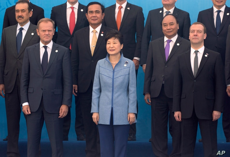 European Council President Donald Tusk, left, South Korea's President Park Geun-hye, center, Russia's Prime Minister Dmitry Medvedev, right, and others pose for a group photo of leaders at the 11th Asia-Europe Meeting (ASEM) in Ulaanbaatar, Mongolia ...
