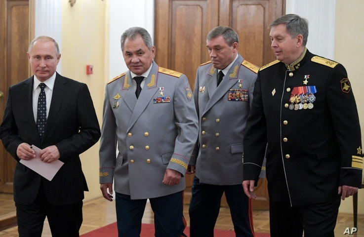 From the left: Russian President Vladimir Putin, Defense Minister Sergei Shoigu, Head of the General Staff of the Armed Forces of Russia and First Deputy Defense Minister Valery Gerasimov, and Deputy GRU chief, Vice Adm. Igor Kostyukov walk to attend...