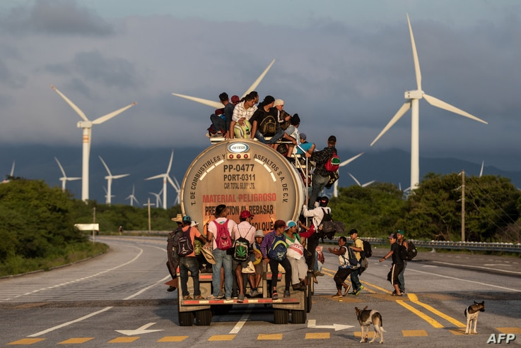 A truck carrying mostly Honduran migrants taking part in a caravan heading to the US, passes by a wind farm on their way from Santiago Niltepec to Juchitan, near the town of La Blanca in Oaxaca State, Mexico, on October 30, 2018.