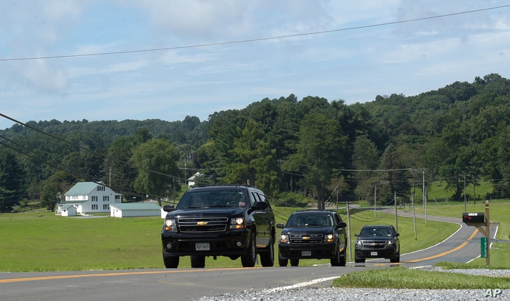 Official vehicles drive down a road near Camp David, Md., Aug. 18, 2017.