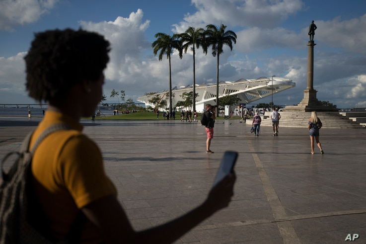 """Gabriele Roza, a reporter for Agencia Publica who helped develope the """"Museum of Yesterday"""" app holds a cell phone in Praca Maua, at the heart of the renovated port area in Rio de Janeiro, Brazil, July 6, 2017."""