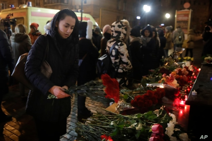 A woman lays flowers at the well-known military choir's building in Moscow, Dec. 25, 2016.