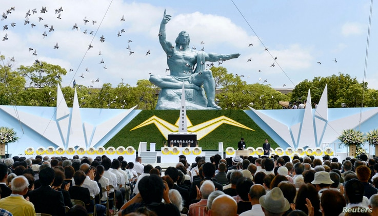 Doves fly near the Peace Statue in Nagasaki's Peace Park in Nagasaki, western Japan, during a ceremony commemorating the 68th anniversary of the atomic bombing of the city, August 9, 2013. (Reuters/Kyodo)