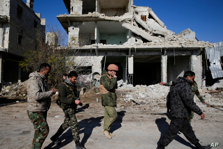 Russian and Syrian army soldiers gather at the last checkpoint before the front line with rebels, in Karam al-Tarab, east of Aleppo, Syria, Dec. 4, 2016.